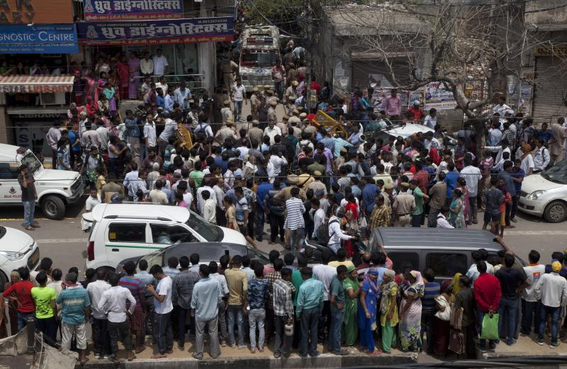 Pedestrians gather near the house where Indian police found 11 bodies in Burari village, north Delhi, India, Sunday, July 1, 2018. Ten bodies, blindfolded by cotton and pieces of cloth, were found hanging from an iron grill used as a ventilator in the home's courtyard, while the body of a 70-year-old woman was lying on the floor of the house, said a police official who spoke on condition of anonymity, in line with department policy. (AP Photo/Rishabh R. Jain)