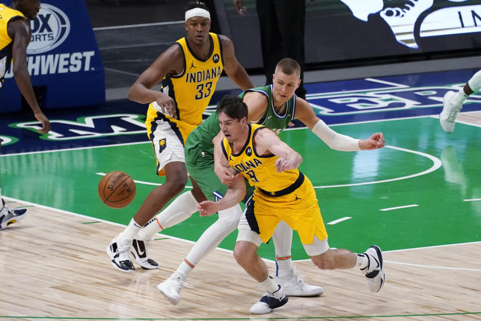 Indiana Pacers guard T.J. McConnell (9) comes away with a steal against Dallas Mavericks center Kristaps Porzingis, middle, as Pacers' Myles Turner (33) watches during the second half of an NBA basketball game in Dallas, Friday, March 26, 2021. (AP Photo/Tony Gutierrez)