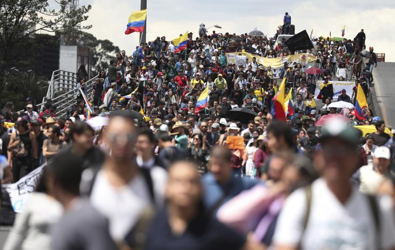Anti-government demonstrators march in Bogota, Colombia, Wednesday, Dec. 4, 2019. Colombia's recent wave of demonstrations began with a massive strike on Nov. 21 that drew an estimated 250,000 people to the streets. Protests have continued in the days since but at a much smaller scale. (AP Photo/Fernando Vergara)