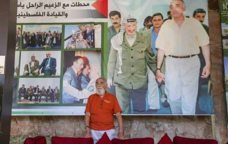 Munib al-Masri stands in front of a poster depicting late Palestinian leader Yasser Arafat at a gallery in his mansion dedicated for the history of Palestinians' struggle