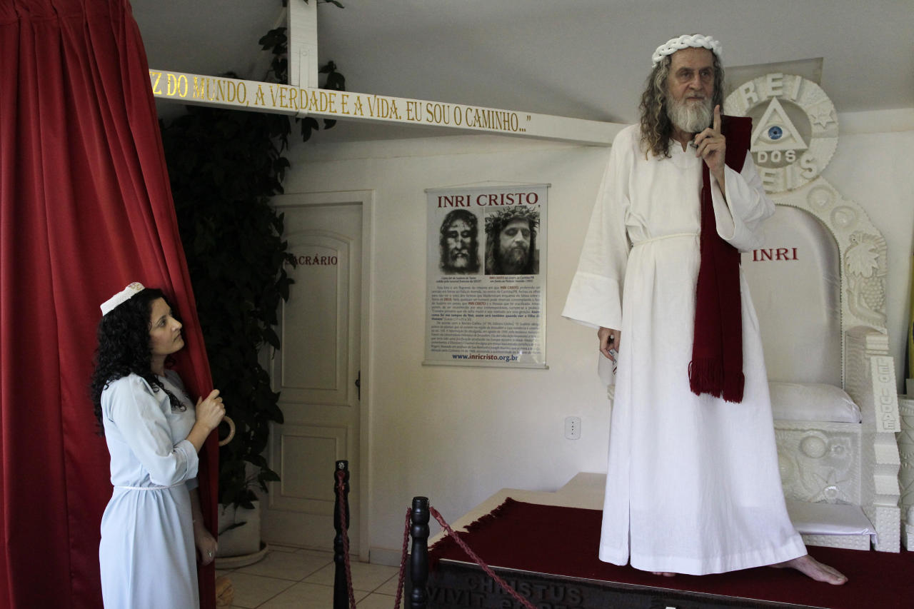 Inri Cristo (R), a Brazilian religious leader who claims to be Jesus Christ reincarnated, gestures on stage as a supporter looks on in Brasilia February 12, 2013. Cristo, who was born Alvaro Theiss in Indaial, Santa Catarina state, Brazil on March 22, 1948, said he is happy that Pope Benedict XVI resigned because he is the 'real son of god.' REUTERS/Ueslei Marcelino (BRAZIL - Tags: RELIGION) - RTR3DPH1