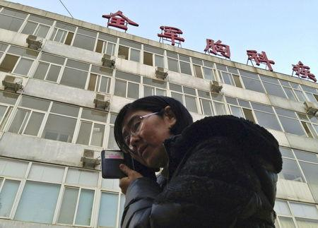 Wang Yu, the lawyer of human right activist Cao Shunli, talks on the phone in front of a hospital building where Cao is hospitalized at its intensive care unit in Beijing in this March 1, 2014 file photo, after she was not allowed to see Cao.  REUTERS/Kim Kyung-Hoon/Files