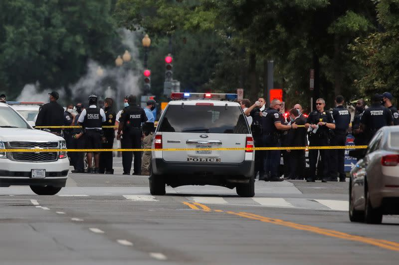 Police officers stand guard after a shooting incident outside of the White House, in Washington