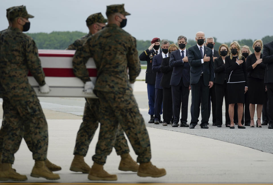 President Joe Biden, first lady Jill Biden, and Secretary of Defense Lloyd Austin look on as as a carry team moves a transfer case with the remain of Marine Corps Sgt. Johanny Rosariopichardo, 25, of Lawrence, Mass., during a casualty return at Dover Air Force Base, Del., Sunday, Aug. 29, 2021, According to the Department of Defense, Rosariopichardo died in a suicide bombing at Afghanistan's Kabul airport, along with 12 other U.S. service members. (AP Photo/Carolyn Kaster)