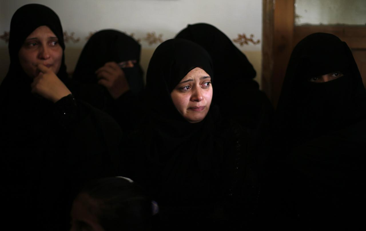 Palestinian relatives of Hamas militant Rabee Baraka wait to take a farewell look at Baraka's body during his funeral at his family's house in Khan Younis in the southern Gaza Strip November 1, 2013. An Israeli air strike killed three militants in the Gaza Strip on Friday, the Islamist group Hamas said, after an overnight clash left a fourth Palestinian gunman, Baraka, dead and five Israeli soldiers wounded. REUTERS/Suhaib Salem (GAZA - Tags: POLITICS CIVIL UNREST TPX IMAGES OF THE DAY)