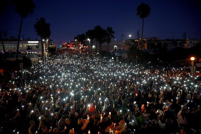 <p>People hold candles and flashlights into the air during a memorial for Rachael Parker and Sandy Casey, Manhattan Beach city employees and victims of the October 1st Las Vegas Route 91 music festival mass shooting, in Manhattan Beach, Calif., Oct. 4, 2017. (Photo: Patrick T. Fallon/Reuters) </p>