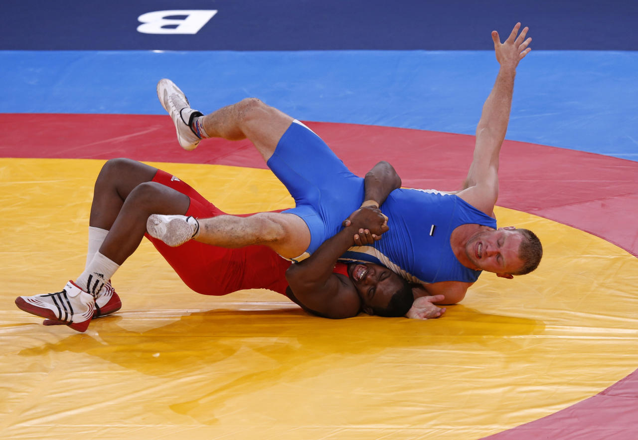Cuba's Mijain Lopez Nunez (in red) fights with Estonia's Heiki Nabi on the final of the Men's 120Kg Greco-Roman wrestling at the ExCel venue during the London 2012 Olympic Games August 6, 2012.                   REUTERS/Kim Kyung-Hoon (BRITAIN  - Tags: OLYMPICS SPORT WRESTLING)