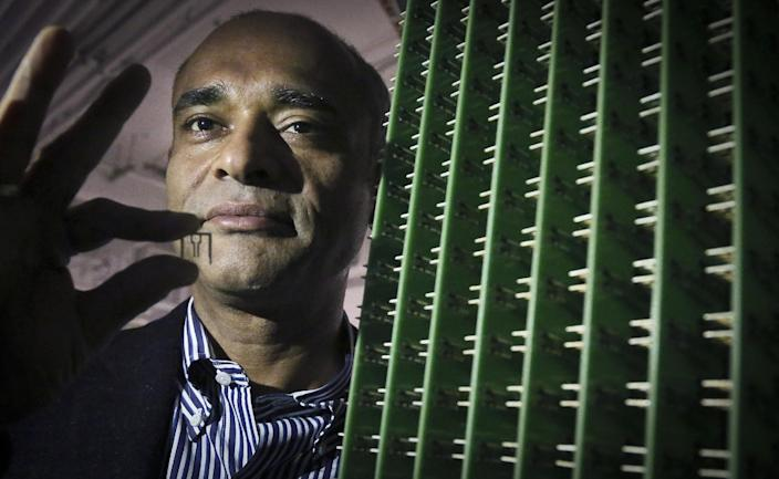 In this Thursday, Dec. 20, 2012, photo, Chet Kanojia, founder and CEO of Aereo, Inc., stands next to a server array of antennas as he holds an antenna between his fingers, in New York. Aereo is one of several startups created to deliver traditional media over the Internet without licensing agreements. Past efforts have typically been rejected by courts as copyright violations. In Aereo's case, the judge accepted the company's legal reasoning, but with reluctance. (AP Photo/Bebeto Matthews)