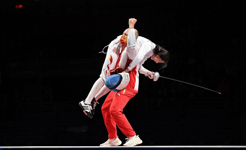 Sun Yiwen is carried over the shoulder of her coach after winning gold for China.