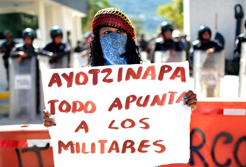 A woman holds a banner during a protest demanding justice in the disappearance of 43 students, on January 12, 2015, at the naval base in Acapulco