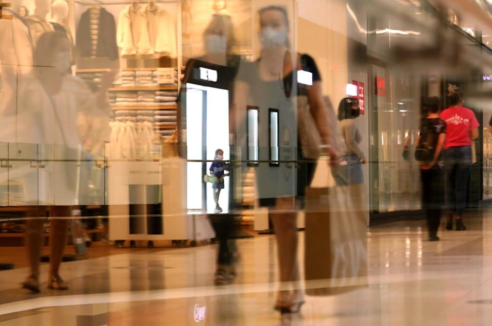 Customers, as seen through a reflection, return to indoor shopping at the Westfield Santa Anita shopping mall.