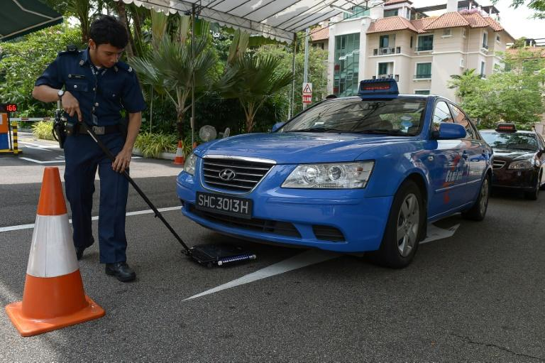 A police officer inspects a car ahead of the meeting between Chinese President Xi Jinping and Taiwan President Ma Ying-jeou, at Shangri-La hotel in Singapore, on November 7, 2015