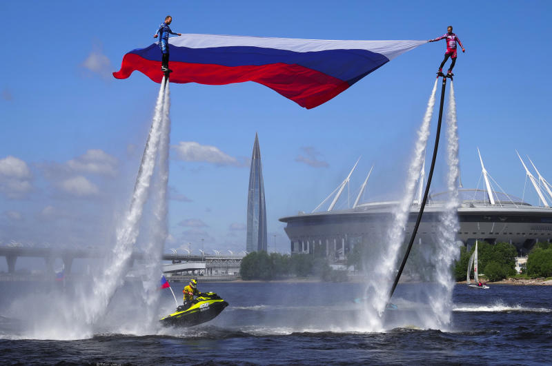 Members of the Russian hydroflight team hold the Russian national flag during the Day of Russia celebration in St.Petersburg, Russia, Friday, June 12, 2020, with business tower Lakhta Centre, the headquarters of Russian gas monopoly Gazprom and Gazprom Arena soccer stadium in the background. (AP Photo/Dmitri Lovetsky)