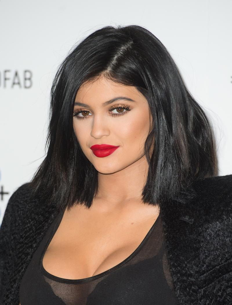 Back to a dark brunette bob, Jenner pairs her her golden smokey with a bold, matte red lip at the Nip+Fab in London.
