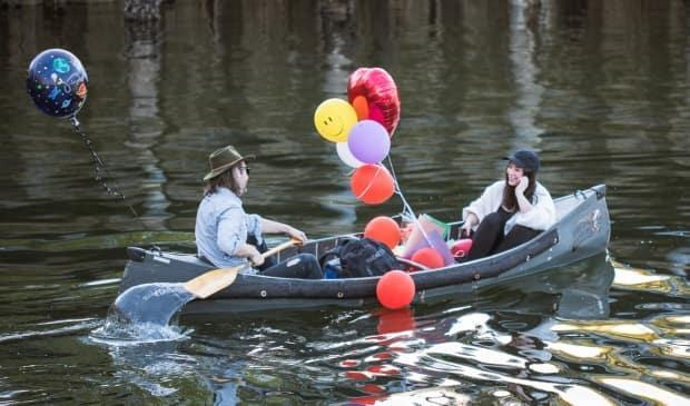 Adrian Glynn McMorran, left, took his partner, Marlene Ginader, on a surprise birthday canoe trip on April 17. The trip featured five stops along Vancouver's False Creek, with friends and gifts at the ready.   (Submitted by Jon McMorran - image credit)