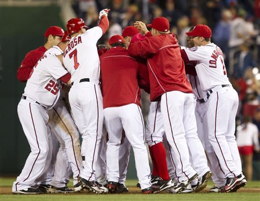 Washington Nationals right fielder Jayson Werth is surrounded by teammates after hitting the game-winning single during the 13th inning of a baseball game against the Cincinnati Reds on Friday, April 13, 2012, in Washington. The Nationals won 2-1. (AP Photo/Evan Vucci)