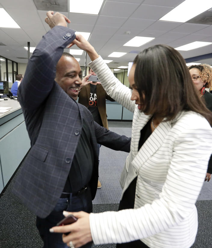 State Attorney Aramis Ayala, right, celebrates with her husband David, a former felon, after he registered to vote at the Supervisor of Elections office Tuesday, Jan. 8, 2019, in Orlando, Fla. Former felons in Florida began registering for elections on Tuesday, when an amendment that restores their voting rights went into effect. (AP Photo/John Raoux)