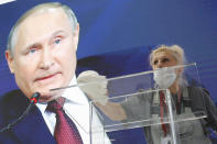 A worker cleans a speaker's podium as Russian President Vladimir Putin seen on a screen in the background at the St. Petersburg International Economic Forum in St. Petersburg, Russia, Friday, June 4, 2021. Russian President Vladimir Putin on Friday praised his country's response to the COVID-19 pandemic and called for a stronger global response to global warming. (AP Photo/Dmitri Lovetsky)