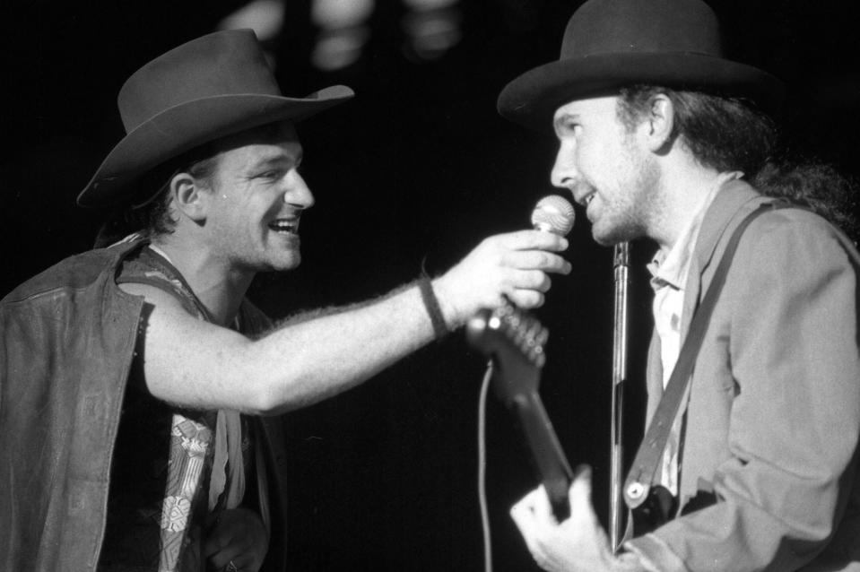 "FOXBOROUGH, MA - SEPTEMBER 22: Lead vocalist Bono, left, holds out a microphone to guitarist The Edge as U2 perform at Sullivan Stadium in Foxborough, MA on Sep. 22, 1987 during the band's tour supporting ""The Joshua Tree."" (Photo by Suzanne Kreiter/The Boston Globe via Getty Images)"