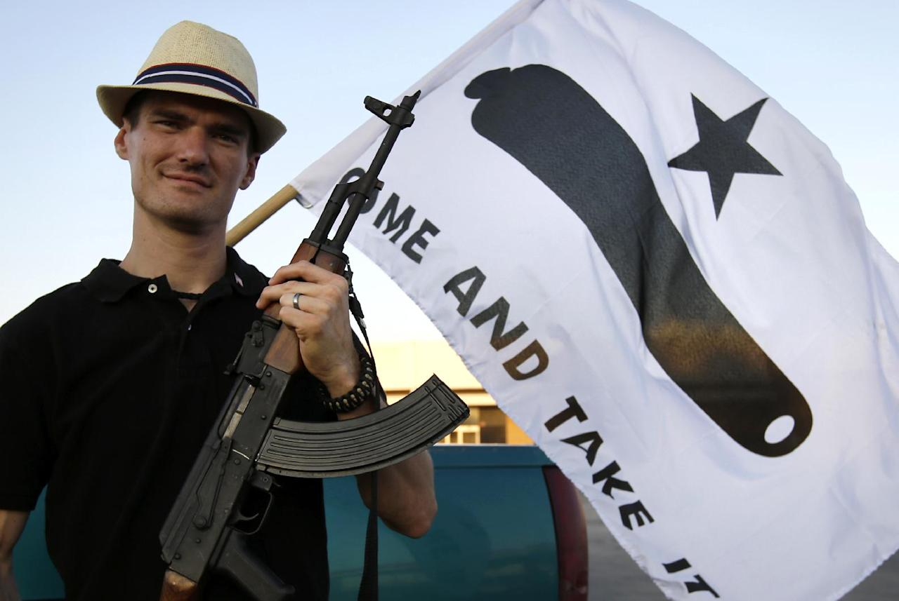 Kory Watkins, coordinator for Open Carry Tarrant County poses for a portrait holding his Romanian AK 47, Thursday, May 29, 2014, in Haltom City, Texas. North Texas gun rights advocates are suing the city of Arlington for amending an ordinance that they claim is discriminatory and infringes upon free speech rights, in the latest sign of growing tensions among gun activists and government forces in Texas. (AP Photo/Tony Gutierrez)