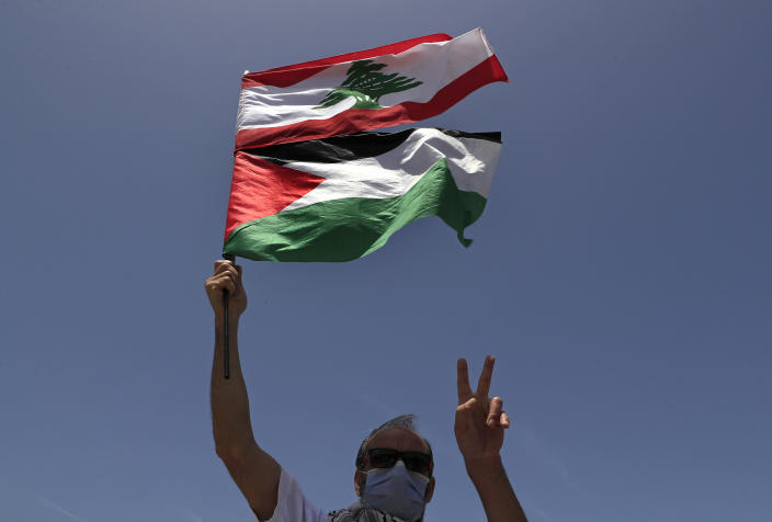 A Lebanese protester flashes a victory sign, as he holds the Lebanese and Palestine flags during a sit-in on a road that leads to a U.N. post along the Lebanon-Israel border known as Ras Naqoura where Lebanese and Israeli delegations are meeting, in Naqoura, Lebanon, Tuesday, May 4, 2021. After a nearly six-month pause, Lebanon and Israel on Tuesday resumed indirect talks with U.S. mediation over their disputed maritime border. (AP Photo/Hussein Malla)