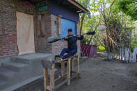 """Kashmiri kayaker Vilayat Hussain practices on a rugged wooden ergometer, or rowing machine, at his home on the outskirts of Srinagar, Indian controlled Kashmir, on April 24, 2020. Like many other athletes, Hussain was restricted to his home due to the coronavirus pandemic. He says he is still constructing the ergometer, which needs a cable and weights to work properly. """"It helps me to maintain my workouts even though it is far from what it should look like."""" (AP Photo/Dar Yasin)"""