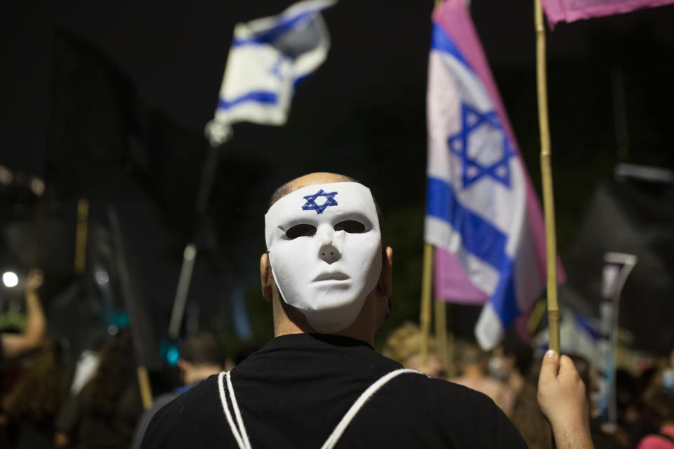 A man wears a mask at a protest outside of Israeli Prime Minister Benjamin Netanyahu's residence in Jerusalem, Saturday, Oct. 24, 2020. Weekly protests have been taking place for the past four months, with crowds calling on Netanyahu to resign over criminal corruption charges and his handling of the coronavirus. (AP Photo/Maya Alleruzzo)