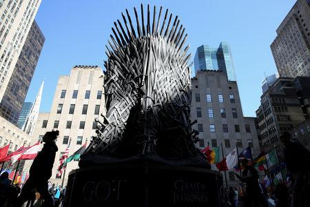 "FILE PHOTO: People walk past a large replica of the iron throne before the premiere of the final season of ""Game of Thrones"" at Radio City Music Hall in New York"