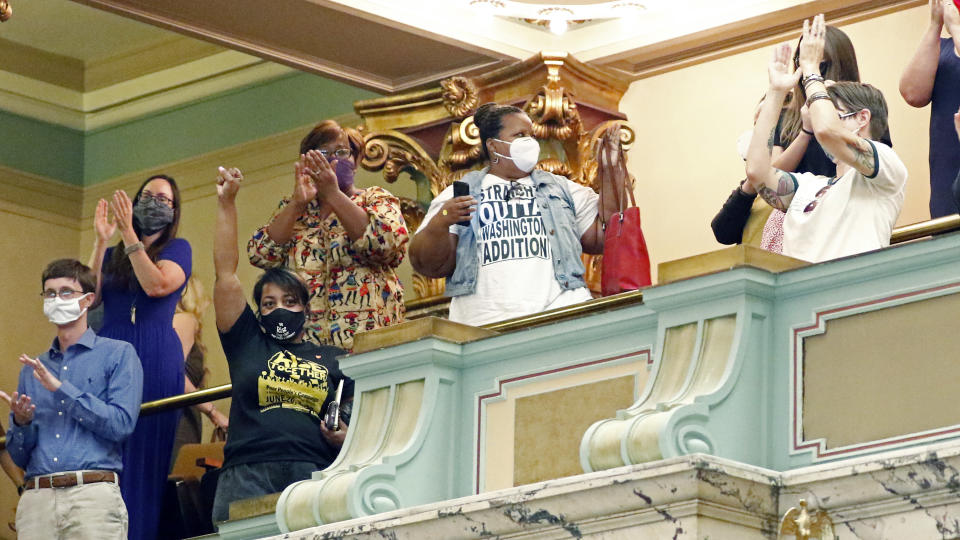 Members of the Mississippi Senate gallery rise and applaud after the body passed a resolution that would suspend the rules to allow lawmakers to change the state flag, Saturday, June 27, 2020 at the Capitol in Jackson, Miss. Members of both the House and Senate are now expected to pass a bill that removes the current flag and establishes a path forward to getting a new one. Gov. Tate Reeves has already said he would sign whatever flag bill the Legislature decides on. The current flag has in the canton portion of the banner the design of the Civil War-era Confederate battle flag, that has been the center of a long-simmering debate about its removal or replacement. (AP Photo/Rogelio V. Solis)
