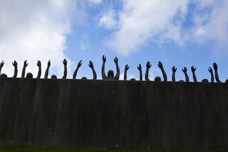 """This photo shows a bronze statue called """"Raise Up"""" as part of the display at the National Memorial for Peace and Justice, a new memorial to honor thousands of people killed in racist lynchings, Monday, April 23, 2018, in Montgomery, Ala. The national memorial aims to teach about America's past in hope of promoting understanding and healing. It's scheduled to open on Thursday. (AP Photo/Brynn Anderson)"""