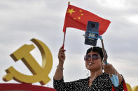 A woman holds a national flag while using a smartphone to film herself with a communist party's logo on display at Tiananmen Square to mark the 100th anniversary of the founding of the ruling Chinese Communist Party in Beijing on Monday, July 5, 2021. Chinese leader Xi Jinping on Tuesday attacked calls from some in the U.S. and its allies to limit their dependency on Chinese suppliers and block the sharing of technologies. (AP Photo/Andy Wong)