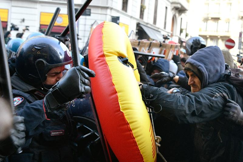 Police officers in riot gear grapple with anti-fascist protesters at a rally in Milan on Saturday (AFP Photo/Piero CRUCIATTI)