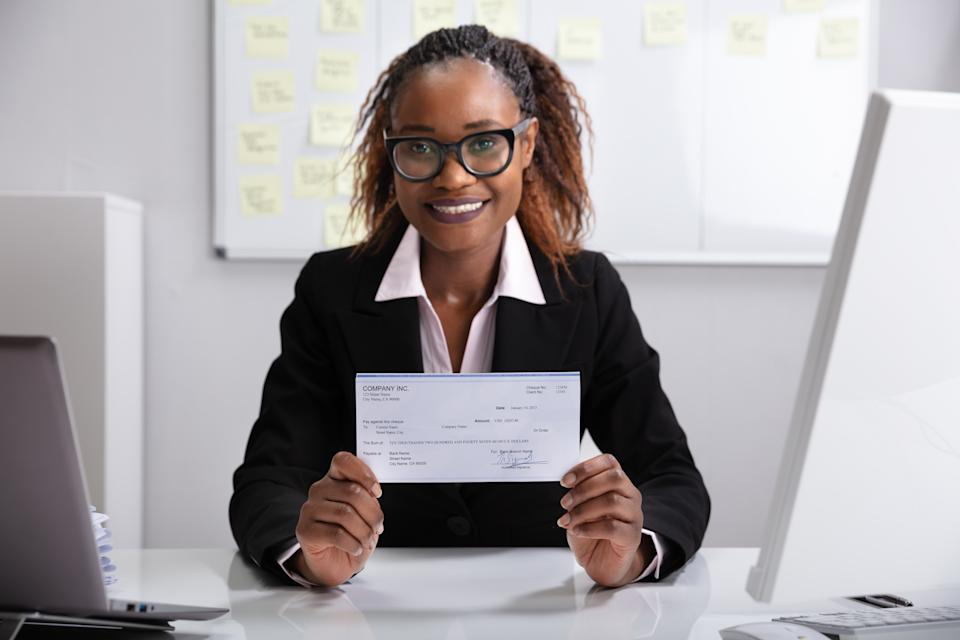 Close-up Of A Smiling Businesswoman Showing Company Cheque