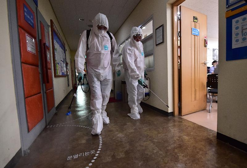 South Korean health officials spray an antiseptic solution while wearing protective gear at an arts centre in Seoul on June 12, 2015 (AFP Photo/Jung Yeon-Je)
