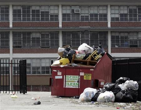 Trash overflows from a container in the parking lot of the Anna B. Pratt Elementary School, in North Philadelphia, shut down after the 2012-2013 school year, in this photo taken in Philadelphia, Pennsylvania September 5, 2013. REUTERS/Tom Mihalek