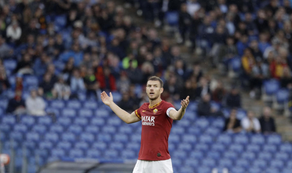 Roma's Edin Dzeko talks to fans as the match was briefly suspended because fans were making racist chants against Napoli's Kalidou Koulibaly, during an Italian Serie A soccer match between Roma and Napoli, at the Olympic stadium in Rome, Saturday, Nov. 2, 2019. (AP Photo/Gregorio Borgia)