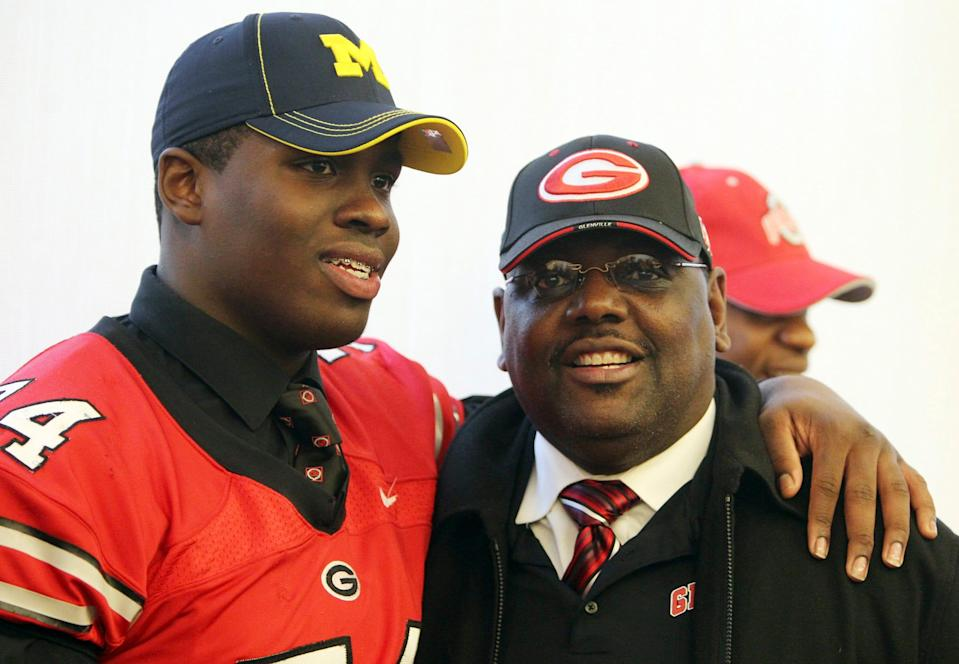 Glenville head coach Ted Ginn, Sr. poses for photographs with player Willie Henry after Willy signed to play for the University of Michigan February 1, 2012 at the Barbara Byrd Bennett Center in Cleveland during National Signing Day.
