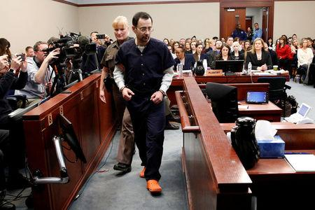 FILE PHOTO: Larry Nassar, a former team USA Gymnastics doctor who pleaded guilty in November 2017 to sexual assault charges, is escorted into the courtroom during his sentencing hearing in Lansing, Michigan, U.S., January 24, 2018. REUTERS/Brendan McDermid/File Photo