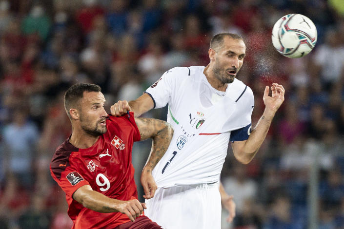 Switzerland's Haris Seferovic, left, fights for a header against Italy's Giorgio Chiellini during the World Cup 2022 group C qualifying soccer match between Switzerland and Italy at the St. Jakob-Park stadium in Basel, Switzerland, on Sunday, Sept. 5, 2021. (Georgios Kefalas/Keystone via AP)
