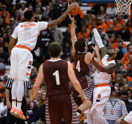Syracuse's Chris McCullough, left, blocks Colgate's Luke Roh's shot as Rakeem Christmas, right, defends during the second half of an NCAA college basketball game in Syracuse, N.Y., Monday, Dec. 22, 2014. (AP Photo/Kevin Rivoli)