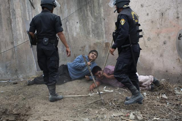 <p>Riot police detain men during a land eviction in Lima, Peru, in May 2015. Hundreds of people were squatting on land that, according to the Ministry of Culture, is an archaeological site. </p>
