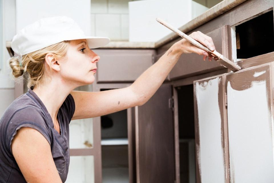 white woman in white hat painting cabinets brown
