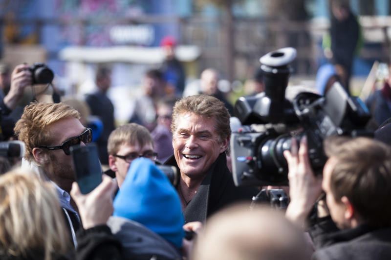 """US actor David Hasselhoff, center, arrives for a protest against the removal of a section of the East Side Gallery, a historic part of former Berlin Wall, in Berlin, Sunday, March 17, 2013. Hasselhoff is fondly remembered by many Germans for releasing a song called """"Looking for Freedom"""" shortly before the fall of the Wall in 1989. (AP Photo/Markus Schreiber)"""