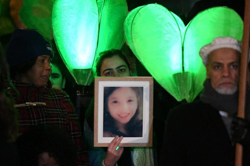 Marchers carried green candles, flowers and pictures of loved ones who died in the fire (REUTERS)
