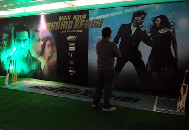 "A Pakistani visitor looks at posters of the forthcoming Pakistani film ""Main houn Afridi"" or ""I am Afridi"" in Karachi on July 7, 2013. A Pakistani film inspired by the fairytale career of cricket star Shahid Afridi goes on release next month, a heart-warming tale of raw talent that producers believe will be a smash hit. Pakistan's film industry has been on the skids for years, unable to compete with India's Bollywood, but filmmakers hope the phenomenal popularity of one of the country's best-loved cricketers will translate into takings at the box office. AFP PHOTO / ASIF HASSAN"