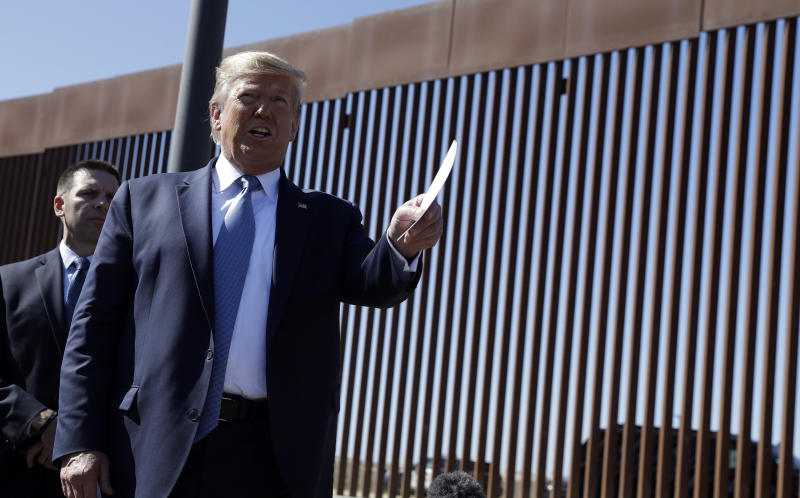 President Donald Trump talks with reporters as he tours a section of the southern border wall, Wednesday, Sept. 18, 2019, in Otay Mesa, Calif., as acting Homeland Secretary Kevin McAleenan listens, (AP Photo/Evan Vucci)