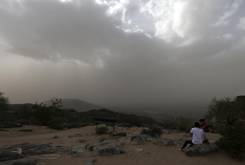 Tourists watch from the top of South Mountain as gusty winds envelop Phoenix in a dusty haze Monday, April 8, 2013. (AP Photo/Ross D. Franklin)