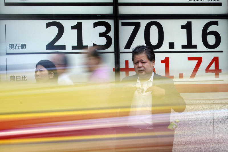 People stand near an electronic stock board showing Japan's Nikkei 225 index at a securities firm in Tokyo Tuesday, Sept. 10, 2019. Asian shares were mixed Tuesday after a day of listless trading on Wall Street, as investors awaited signs on global interest rates.(AP Photo/Eugene Hoshiko)