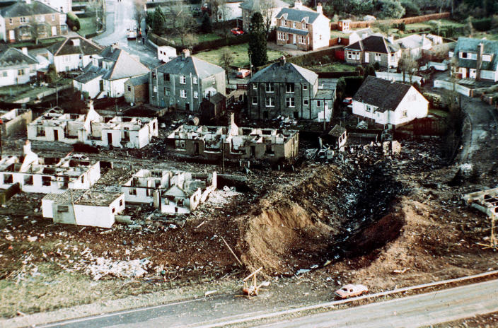 FILE - This December 1988 file photo shows wrecked houses and a deep gash in the ground in the village of Lockerbie, Scotland, after the bombing of the Pan Am 103 in the village of Lockerbie, Scotland. The Justice Department expects to unseal charges in the coming days in connection with the 1988 bombing of a Pan Am jet that exploded over Lockerbie, Scotland, killing 270 people, according to a person familiar with the case. (AP-Photo/Martin Cleaver, File)