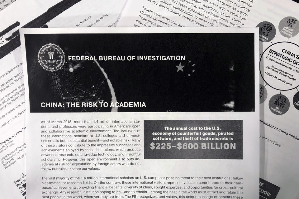 This Oct. 4, 2019 photo shows a copy of an FBI pamphlet and related emails. The Trump administration says it will soon require Chinese officials in the U.S. to notify the State Department ahead of any contacts they plan to have with American educators, researchers and local and state governments. (AP Photo)